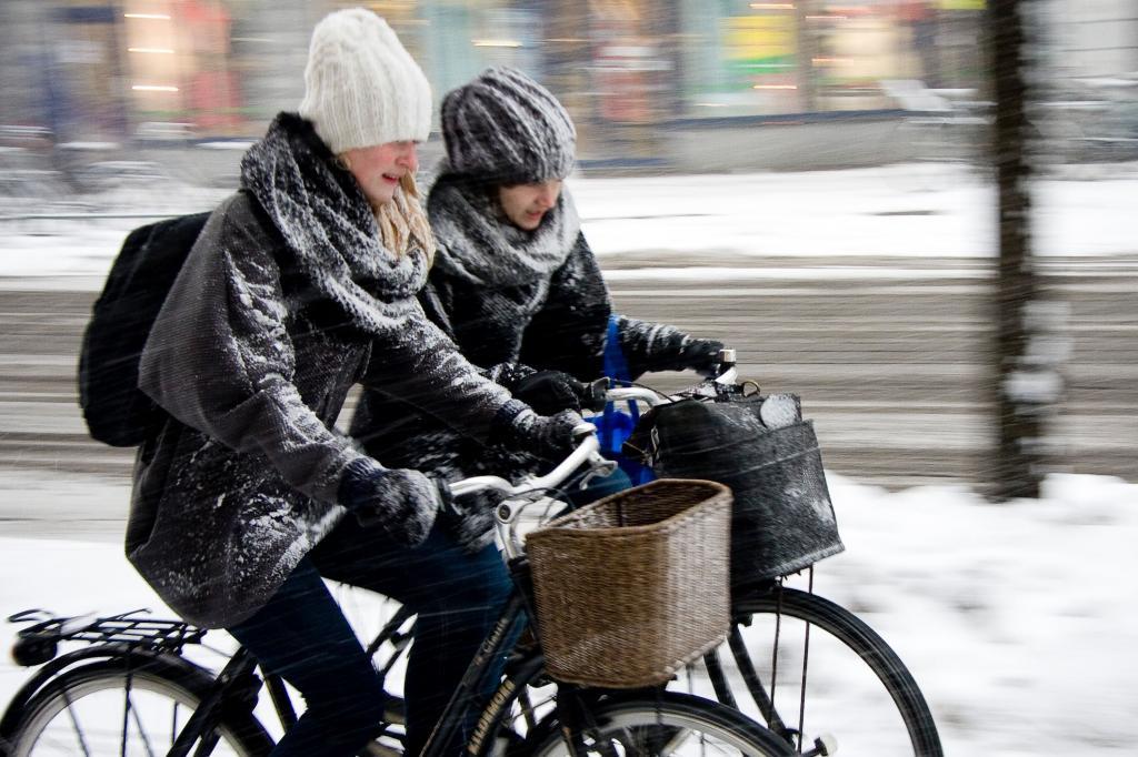 Девушки попали под снегопад на велосипедах.