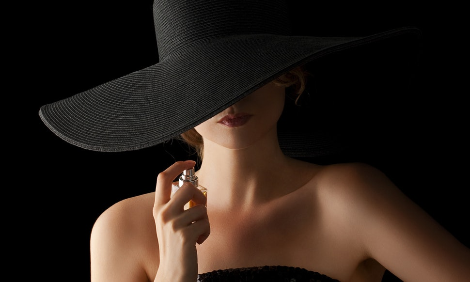 Girl in a hat with a perfume bottle