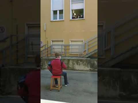 Дедушка исполняет серенаду на аккордеоне своей жене под окнами больницы